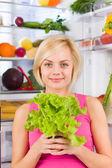 Woman holds green salad — Стоковое фото