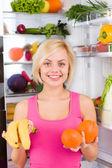 Woman holds banana and orange — Stockfoto