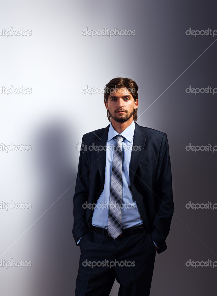 时尚商务男人,英俊的男模特穿西装打着领带在灰色背景— photo by