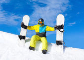 Snowboarder sitting snow slope with snowboards — Foto Stock