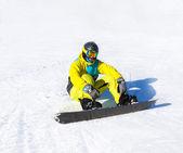 Snowboarder sitting on snow mountains — Stock Photo