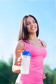Woman holding bottle of water on stadium — Stock Photo