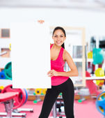 Fitness woman holds blank board — Stock Photo
