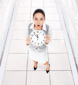 Worried businesswoman holding clock — Stock Photo