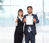 Business couple showing tablet pc and smart phone — Stock Photo