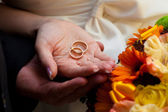Wedding rings on hands of newlyweds — Stock Photo