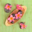 Frangipani and polished stone on bamboo mat — Foto de Stock