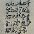 Alphabet letters handwritten in sand on beach — Stock Photo