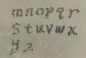 Alphabet letters handwritten in sand on beach — Stock Photo