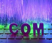 Fiberoptik bakgrund med com — Stockfoto