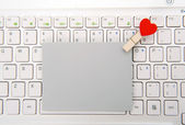 Laptop keyboard with small red hearts clothes pegs and sticky note — Stock Photo