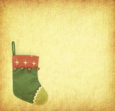 Red Christmas stocking on grunged paper background — Stock Photo