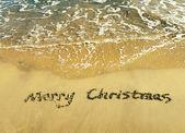 Merry Christmas handwritten in sand on beach — Stock Photo