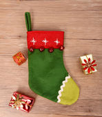 Christmas sock with gifts on wooden background — Stock Photo