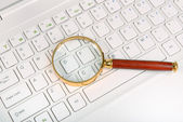 Magnifying glass on laptop computer — Stock Photo