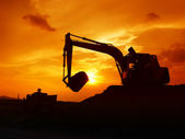Digger shovel working at sunset — Stock Photo