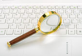 Laptop with a magnifying glass — Stock Photo