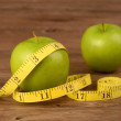 Diet concept,two apples and measuring tape on wood background — Stock Photo