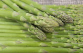 Fresh green asparagus sprouts laying on bamboo background — Stock Photo