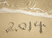 Year 2014 hand written on the white sand in front of the sea — Stock fotografie