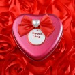 Red heart decoration with wedding candy box on rose background — Stock Photo #47275287