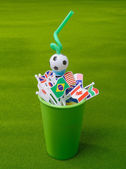 Drinking straw in green cup with many nation flag — Stock Photo