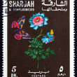 Postage stamp Sharjah 1967 Anemone Flower and Butterfly, circa 1 - Stock Photo