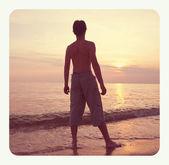 Boy silhouette on beach — Stockfoto