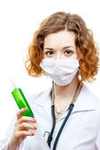 Cute redhead doctor in lab coat with syringe in mask — Stockfoto