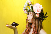 Calm pretty girl with snail and flower crown on head — Stock Photo
