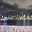 Hongkong cityscpae skyline at night,wood footpath pavement by the victoria sea. — Stock Photo