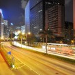 The traffic light trails in the street by modern building in Wanchai,the prosperous business center in Hongkong. — Stock Photo