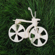 Foto Stock: White wood toy bicycle on verdure grass.