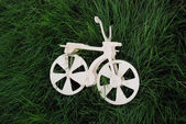 The white wood toy bicycle on the verdure grass. — Stock Photo