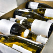 White wine in bottles in wine shop - Stock Photo