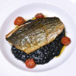 Sea bass (black sea bass) served with black risotto — Stock Photo