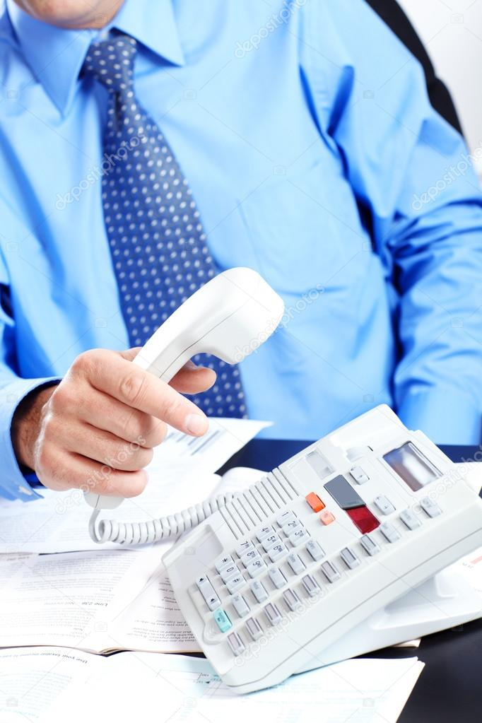 Businessman in a blue shirt with telephone in the office  — Stock Photo #13518121