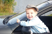 The boy looks out from the automobile — Stock Photo