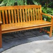 Wooden bench is in a green park — Stock Photo #14035766