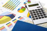 Miniräknare och diagram på en business-bakgrund — Stockfoto