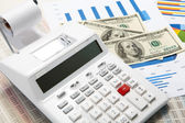 Calculator and diagrams and money on a business background — Stock Photo