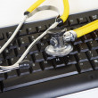 Yellow phonendoscope and black keyboard — Stock Photo