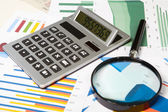 Calculator and magnifier — Stock Photo