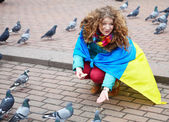 The girl with a flag feeds the pigeons on the square — Stock Photo