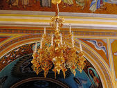 Gold ornated luxurious luster in interior of church — Stok fotoğraf
