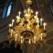 Gold ornated luxurious luster in interior of church - Stock Photo