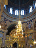 Gold ornated luxurious luster in interior of church — Stock Photo