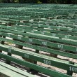 Rows of simple green seats near empty outdoors scene — Stock Photo #27357623