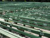 Rows of simple green seats near empty outdoors scene — Stock Photo