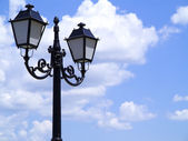 Old street decorated lamppost against cloudy blue sky — Stock Photo